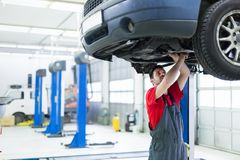 Car mechanic working at automotive service center. Handsome car mechanic working at automotive service center royalty free stock photography