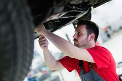 Car mechanic working at automotive service center. Handsome car mechanic working at automotive service center Royalty Free Stock Images