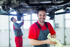 Car mechanic working at automotive service center. Handsome car mechanic working at automotive service center Royalty Free Stock Photo