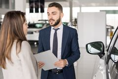 Handsome Car Salesman Consulting Woman. Waist up portrait of handsome car salesman talking to client in car showroom helping her choose Stock Image