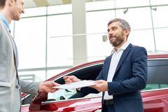 Handsome Car Salesman Giving Contract to Client. Waist up portrait of smiling bearded salesman handing purchase papers to client buying brand new car in luxury Royalty Free Stock Images