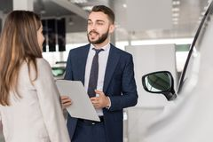 Handsome Car Salesman Selling Cars. Portrait of handsome car salesman talking to young women helping her choose  in car showroom Royalty Free Stock Photos