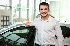 Handsome car salesman showing thumb up gesture. Near automobile in dealership centre stock image