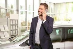 Handsome car salesman talking on phone. In dealership centre stock images