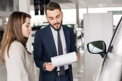 Handsome Car Salesman Talking to Client. Waist up portrait of handsome car salesman talking to young woman helping her choose  in car showroom Stock Photography