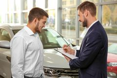 Handsome car salesman with trainee. In dealership centre Royalty Free Stock Images