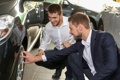 Handsome car salesman with trainee looking at automobile. In dealership centre Royalty Free Stock Photography