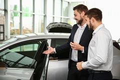 Handsome car salesman with trainee looking at automobile. In dealership centre Stock Image