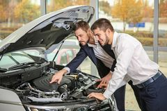 Handsome car salesman with trainee looking at automobile`s engine. In dealership centre stock photos