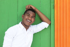 Handsome caribbean guy in front of a colorful wall. Laughing at camera stock image