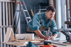 Handsome carpenter working in workshop royalty free stock photo