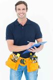 Handsome carpenter writing on clipboard Royalty Free Stock Photo