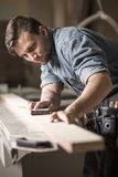 Handsome carpentry employee grinding board Stock Image