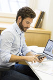 Handsome casual business man working on computer in modern offic Stock Photos