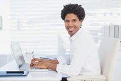 Handsome casual businessman smiling at camera working on laptop. In his office Stock Image