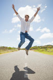 Handsome casual man leaping on a road smiling at camera Royalty Free Stock Images