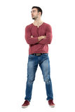 Handsome casual man in red v-neck shirt and jeans with crossed arms looking away. Full body length portrait isolated over white background Stock Photo