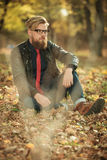 Handsome casual man sitting in the park Royalty Free Stock Image