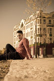 Handsome casual man sitting on the sidewalk in  old city Stock Images