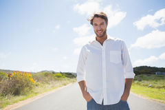 Handsome casual man standing on a road smiling at camera Stock Photo