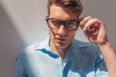 Handsome casual man taking off his glasses. Royalty Free Stock Image