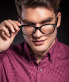 Handsome casual man taking off his glasses Royalty Free Stock Image
