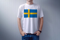 Handsome casual man wearing white t-shirt with Swedish flag Royalty Free Stock Images