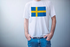 Handsome casual man wearing white t-shirt with Swedish flag Stock Images
