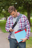 Handsome casual student standing and texting Royalty Free Stock Photo