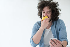 Young man eating apple and using a mobile phone  at home Stock Photos