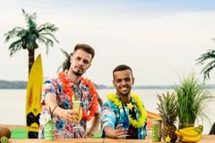 Handsome caucasian bartender and Latin American barman standing. Near the bar counter and holding cocktails on the ocean. Concept of preparation, relaxing and royalty free stock image