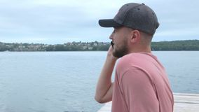 Man talking phone while sitting near wide lake in slow motion stock video footage
