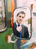 Handsome caucasian business man correcting his tie looking at  rear view mirror of retro bus Stock Image