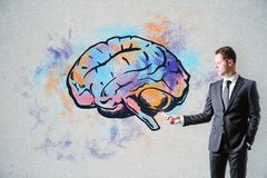 Brain storm and leadership concept. Handsome caucasian businessman drawing creative brain sketch on concrete wall background. Brain storm and leadership concept Royalty Free Stock Images