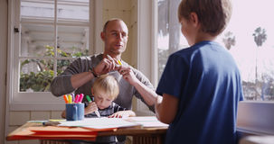 Handsome caucasian father doodling with his two boys.  Stock Photo