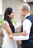 Handsome Caucasian groom talking with his biracial bride outdoor. S. Diverse couple Stock Photos