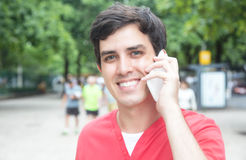 Handsome caucasian guy in red shirt with phone in a park Royalty Free Stock Images