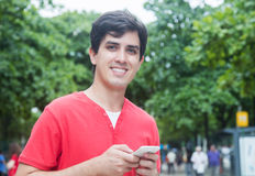 Handsome caucasian guy in red shirt using wifi with phone in a p Stock Image