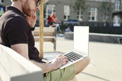 Handsome caucasian hipster man working on laptop sitting outdoor in a park. Summer sunshine day. Concept of young business people royalty free stock photography