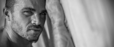 Handsome Caucasian Male Model posing in black and white portrait. Black and white portrait of fashionable white tanned male model posing on the beach and leaning royalty free stock image