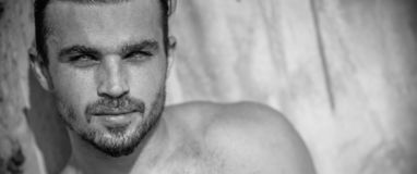 Handsome Caucasian Male Model posing in black and white portrait. Black and white portrait of fashionable white tanned male model posing on the beach and leaning stock images