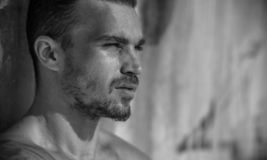 Handsome Caucasian Male Model posing in black and white portrait. Black and white portrait of fashionable white tanned male model posing on the beach and leaning stock photography