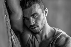 Handsome Caucasian Male Model posing in black and white portrait. Black and white portrait of fashionable white tanned male model posing on the beach, leaning on royalty free stock image