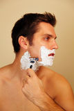 Handsome Caucasian male shaving. With shaving foam and a razor Stock Images