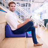 Handsome caucasian male smiling at camera while holding smartphone. Square image of young handsome white male sitting on a colourful cushion in his local co Royalty Free Stock Images
