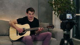 Handsome caucasian man in black T shirt making video blog about musical instruments or recording the song for his
