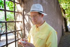Caucasian man in early fifties using smartphone by Italian viney. Handsome Caucasian man in early fifties wearing a white hat using cellphone while standing on Stock Photography