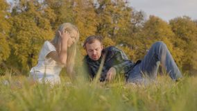 Handsome caucasian man laying on the autumn grass and reading book to a young blonde girl. Father and daughter dressed. In casual clothes spending time together stock video footage