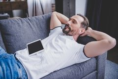 Man listening music in earphones. Handsome caucasian man listening music in earphones using digital tablet Royalty Free Stock Image