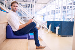 Handsome caucasian man looking at camera with cellphone in hand Royalty Free Stock Images